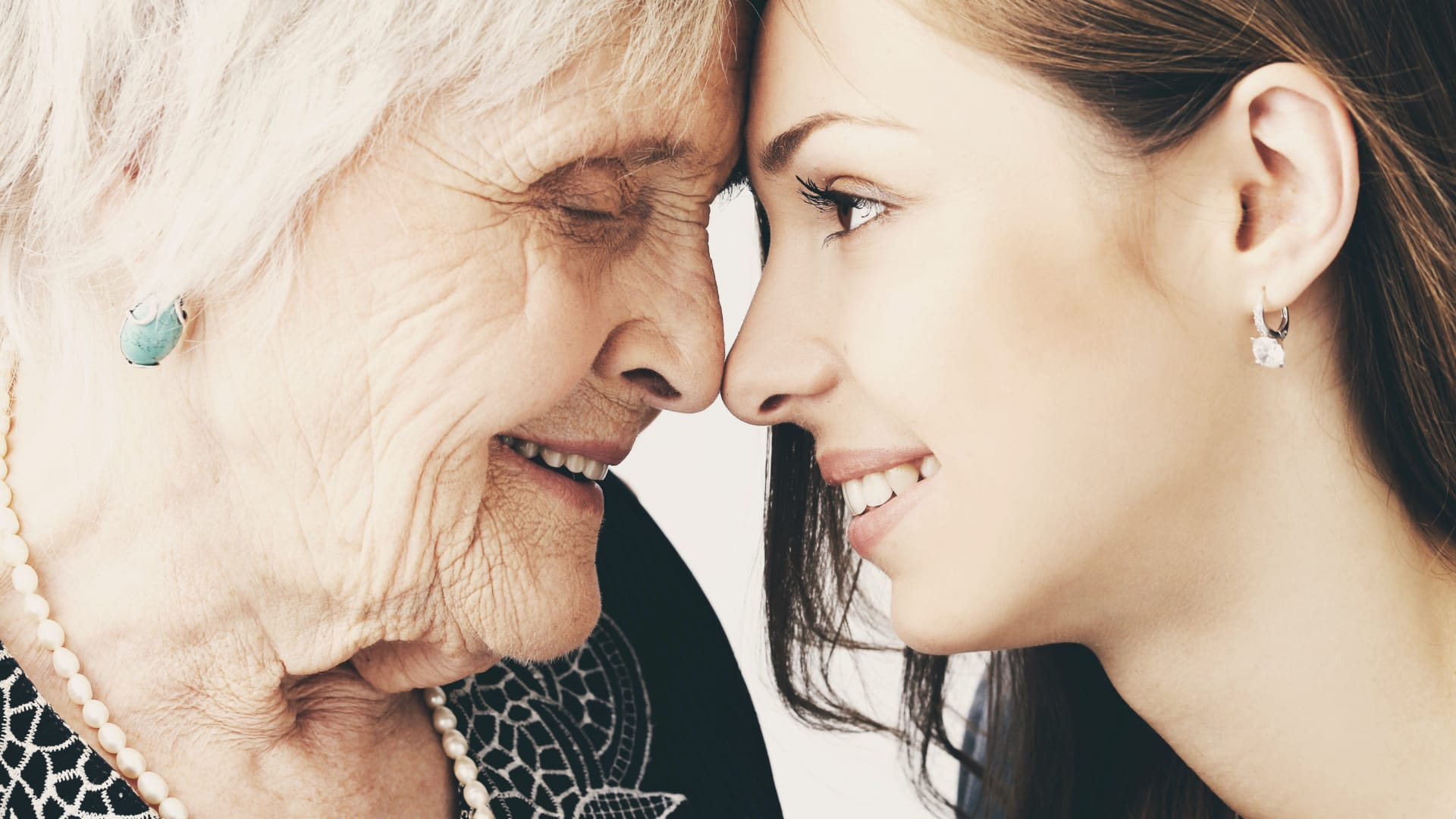 Older woman and young woman with foreheads touching, smiling.
